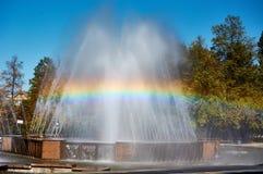 Springbrunnen och regnbågen i staden parkerar arkivfoto