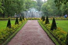 Springbrunnen solen och fågelaviariet i trädgården av lägre parkerar Arkivbilder
