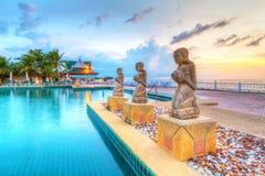 Springbrunnstatyer på den tropiska simbassängen på solnedgången Royaltyfri Bild