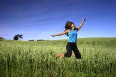 Springen auf ein grünes Feld Stockbilder