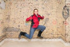 Springen craftswoman met duimen omhoog voor bakstenen muur in bar Stock Afbeeldingen