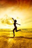 Springen in die Sonnenuntergangstrahlen Stockfotos