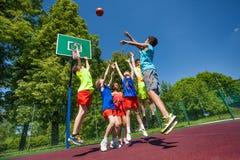 Springen für die Balljugendlichen, die Basketballspiel spielen Stockfotografie