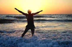 Springen für Freude im Sonnenuntergang auf dem Ozean Stockfotografie