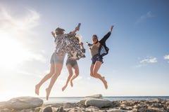 Springen junge Frau drei für Glück Schönheit und Spaß lizenzfreie stockfotografie