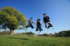 Springen mit drei junges Freunden Lizenzfreie Stockfotografie