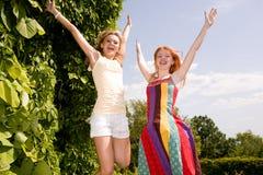 Springen mit zwei glückliches Mädchen Stockbilder