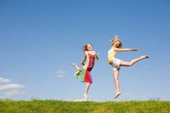 Springen mit zwei glückliches Mädchen Lizenzfreies Stockfoto