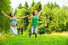 Springen mit zwei jungen Frauen Stockfotografie