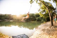 Springen Sie in das Wasser Ein Mann steht auf der Natur still Ein Schwingen von einem Seil und von einem Stock Aktive Erholung in lizenzfreie stockfotos