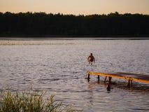 Springen Sie den Kerl in den Fluss bei Sonnenuntergang stockbild