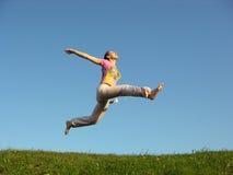 Springen Sie Mädchen unter Himmel Stockfoto