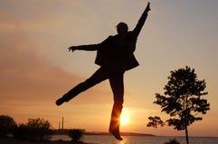 Springen Sie Mann auf Sonnenuntergang Stockfotografie