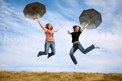 Springen Sie mit den Regenschirmen Stockbild
