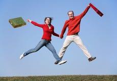 Springen Sie Paare mit Beuteln lizenzfreie stockfotografie
