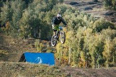 Springen Sie Skirennläufer auf der Mountainbike im abschüssigen Rennen Lizenzfreies Stockfoto