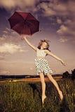 Springend meisje met paraplu stock afbeelding