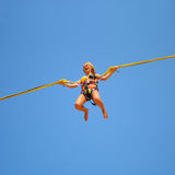 Springend meisje op de trampoline bij funfair stock afbeeldingen