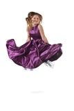 Springend meisje in violette kleding Stock Foto