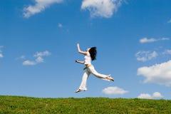 Springend meisje in weide Stock Afbeelding