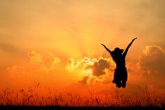 Springend vrouw en zonsondergangsilhouet stock afbeeldingen