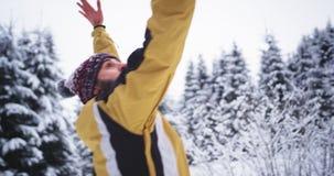 Springende en glimlachende jonge toerist in de winter, vond hij een verbazend sneeuwbos hij geheugen met telefoonfilm neemt stock footage