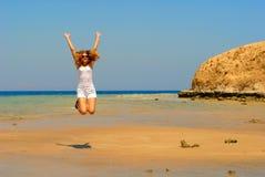 Springende Frau auf der Küste Stockfotografie