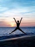 Springende Frau des Schattenbildes auf dem Strand Stockfotos