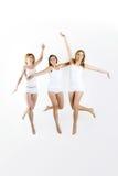 Springende Frauen auf weißem Hintergrund Stockbilder