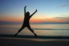 Springende Frauenschattenbilder mit Sonnenaufgang Stockfoto