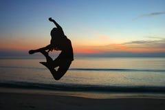 Springende Frauenschattenbilder mit Sonnenaufgang Stockbild