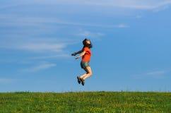 Springende glückliche Gefühlfrau auf Gras- und Himmelhintergründen Stockbild