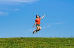 Springende glückliche Gefühlfrau auf Gras- und Himmelhintergründen Lizenzfreies Stockfoto