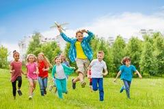 Springende jongen groot vliegtuigstuk speelgoed houden en kinderen die royalty-vrije stock foto