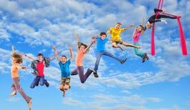 Springende Kinder des glücklichen Tanzens im Himmel Stockbild