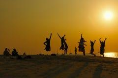 Springende Leute auf dem Strand Lizenzfreies Stockbild