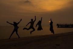 Springende Leute auf Sonnenuntergangzeit Lizenzfreie Stockbilder