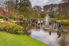 Springende Leute im Th entsteinen Weise im Wasser im Park bei Keukenhof Stockfotografie