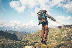 Springende Levitation des glücklichen Mannes mit schwerem Rucksack lizenzfreie stockbilder