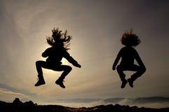 Springende Mädchen, die Spaß haben Stockbild