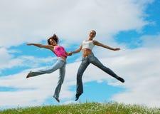 Springende meisjes op weide royalty-vrije stock afbeeldingen