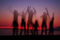 Springende mensen in zonsondergang stock afbeeldingen