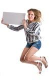 Springende sexy vrouw met een lege witte die raad op wit wordt geïsoleerd Royalty-vrije Stock Afbeelding