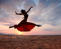 Springende vrouw bij zonsondergang Royalty-vrije Stock Afbeeldingen