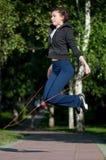 Springende vrouw met touwtjespringen bij park Stock Foto's