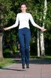 Springende vrouw met touwtjespringen bij park Royalty-vrije Stock Foto's