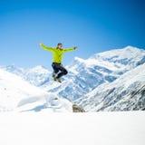 Springender Erfolg des glücklichen Mannes in den Bergen stockbild