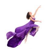 Springender Mädchentänzer, wenn purpurrotes Kleid geflogen wird Stockfotografie