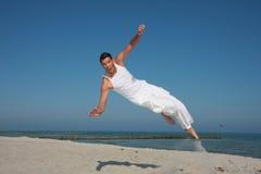 Springender Mann, der hoch auf den Strand fliegt stockbilder