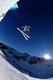 Springender Skifahrer in der Sonne auf blauem Himmel Stockbild
